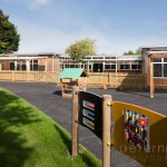 Infant school playground with outdoor equipment in front of timber clad single story classrooms