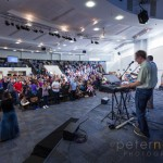Congregation participating in contemporary worship music during Sunday Service inside the large modern Kings Community Church