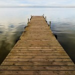 Wooden jetty perspective onto lake without people