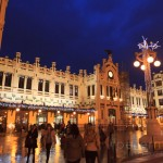 Travellers entering the exterior of the main railway station Estacio del Nord in Valencia lit up on a rainy night