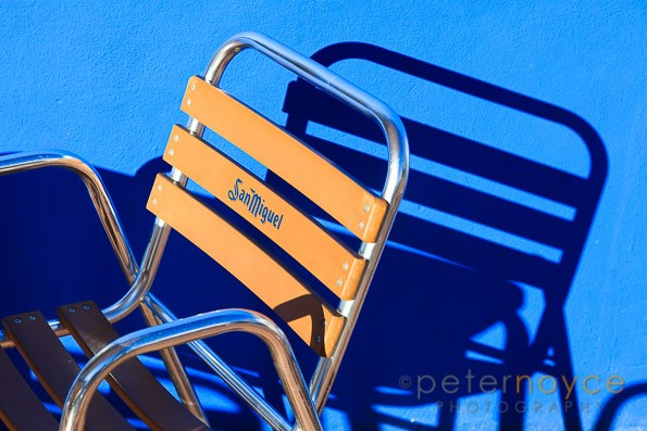 Strong graphic image of San Miguel branded frame chair and sunlight casting shadow on blue wall