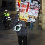 Man carrying protest placard through city streets followed by police motorcyclist