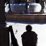 A man with guitar in case sitting waiting in the Plaza de la Seu Valencia Spain