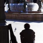 A man with guitar in case sitting waiting in the Plaza de la Seu Valencia Spain