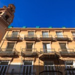 The tower of the Church of Saint Lorenzo and  a residential building with wrought iron balconies in Valencia Spain