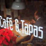 Cafe and Tapas sign on window with diner eating inside
