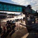 Passengers walking to board airplane under jet bridge