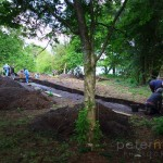 Archaeologists working on a Bronze Age excavation trench in a forest
