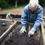 Archaeologists dry sieving in a shaker frame on a dig